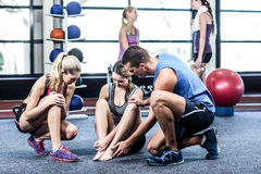 Trainer helping woman with painful ankle. Trainer helping women with painful ankle at the gym Royalty Free Stock Photo