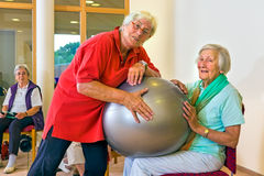Trainer helping woman with stability ball. Physical therapist working with smiling senior women using a silver stability ball for fitness at an old-age home Stock Images