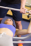 Trainer helping woman to lift the barbell bench press in gym. Closeup of a male trainer helping young fit women to lift the barbell bench press in the gym Royalty Free Stock Image