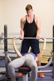 Trainer helping woman to lift the barbell bench press in gym. Male trainer helping young fit women to lift the barbell bench press in the gym Royalty Free Stock Photography