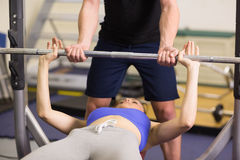 Trainer helping woman to lift the barbell bench press in gym. Male trainer helping young fit women to lift the barbell bench press in the gym Royalty Free Stock Photos