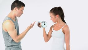 Trainer helping a woman to lift weights stock video footage