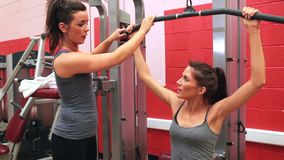 Trainer helping woman on weights machine stock footage