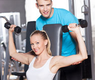 Trainer helping a woman work out with dumbbells Stock Photography