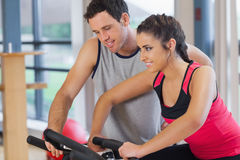 Trainer helping woman work out at spinning class Stock Photos