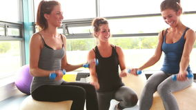 Trainer helping women on exercise balls lifting weights. In gym stock footage