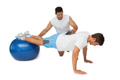 Trainer helping young man exercise on fitness ball. Side view of a male trainer helping young men exercise on fitness ball over white background Stock Image
