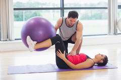 Trainer helping young woman with fitness ball at gym. Side view of a trainer helping young women with fitness ball at a bright gym Royalty Free Stock Photo