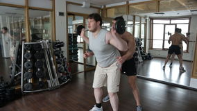 Trainer helps the beginner to do squats with barbell. He looks that learner does all the movements correctly and insures him in case of unexpected loss of stock footage