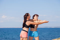 Trainer helps the girl to do the exercises Stock Image