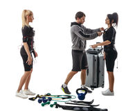 Trainer helps women to set EMS suit Royalty Free Stock Photos