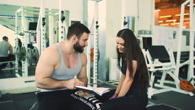 Trainer helps young strong brunette woman write training program in fitness club and gym center. Trainer helps young strong brunette woman write training program stock video footage