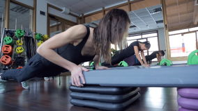 Trainer with her group of women push-up from special benches in studio. Young slim woman in black training suit, grey snickers, with flowing disheveled dark stock video