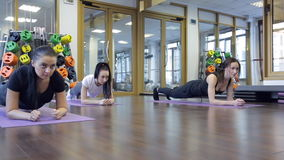 Trainer with her group of women stand pose of plank on mat in gym. stock video footage