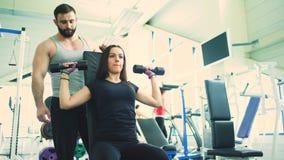 Trainer hilft der jungen starken Brunettefrau, die Übung in der Fitness-Club- und Turnhallenmitte tut stock video