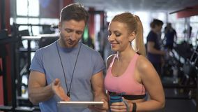 Trainer and his attractive female client discussing workout program in gym. Stock footage stock footage
