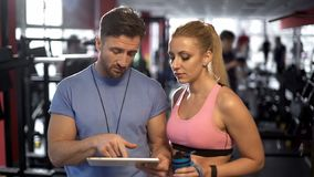 Trainer and his attractive female client discussing workout program in gym stock photography