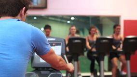 Trainer and his female spinning class. At gym stock footage