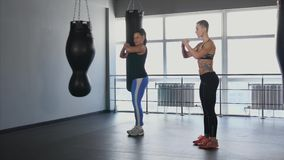 The trainer and his pupil do exercises for the development of musculature. The coach and his pupil do synchronous exercises for development of gluteal muscles stock footage