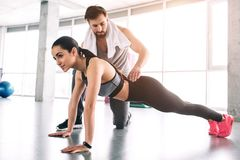 Trainer and his student are in a fitness room. She is doing high plank exercise while he is controlling the quality of stock images