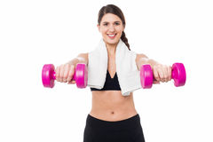 Trainer holding dumbbells in her outstretched arms Royalty Free Stock Images