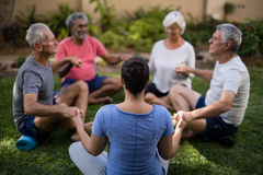 Trainer holding hands and meditating with senior men and women Stock Images