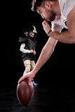 Trainer holding rugby ball and boy preparing to play american football. On black background Stock Photos