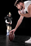 Trainer holding rugby ball and boy preparing to play american football. On black background Royalty Free Stock Photos