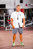 Trainer inside gym. Happy male trainer inside gym Royalty Free Stock Photography