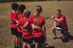Trainer instructing kids in the boot camp. On a sunny day stock images