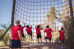 Trainer instructing kids in net climbing during obstacle course training Royalty Free Stock Photography