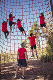 Trainer instructing kids in net climbing during obstacle course training Stock Photography