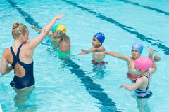 Trainer instructing students in swimming pool Stock Photos