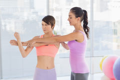 Trainer instructing young woman. Trainer instructing young women at fitness studio Stock Photos