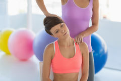 Trainer instructing young woman. Trainer instructing young women at fitness studio Royalty Free Stock Photo