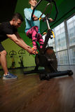 Trainer instructs girl on simulator. In gym Royalty Free Stock Photos