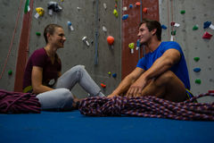 Trainer interacting with athlete while sitting on floor at gym Royalty Free Stock Images