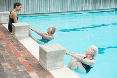 Trainer interacting with senior women at poolside Royalty Free Stock Photos