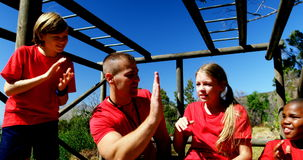 Trainer and kids relaxing during obstacle course training stock footage