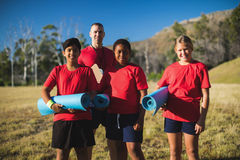 Trainer and kids standing together in the boot camp. Portrait of trainer and kids standing together in the boot camp Royalty Free Stock Photography