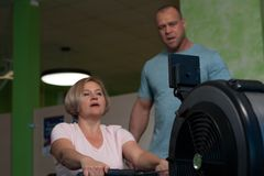 Trainer leads a middle-aged woman s workout royalty free stock photo