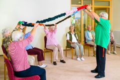 Trainer lifting garland for class with seniors. Royalty Free Stock Image