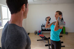 Trainer looking at female athlete lifting kettlebells at club. Male trainer looking at female athlete lifting kettlebells at club Royalty Free Stock Image