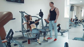 Trainer looking at sportswoman doing exercise. Brunette young woman performing bench press exercise while trainer watching her technique stock video footage