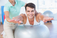 Trainer with man on exercise ball. Trainer with men on exercise ball in fitness studio Stock Images