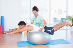 Trainer with man on exercise ball. Trainer with men on exercise ball in fitness studio Stock Image