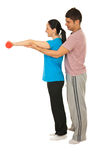 Trainer man helping woman. Trainer men helping women to doing exercises with dumbbell isolated on white background Royalty Free Stock Images