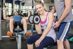 Trainer man helping woman lifting dumbbell Stock Photo