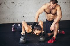 Trainer man and woman push-up strength pushup in a fitness workout. Gym men and women push-up strength pushup in a fitness workout stock photo
