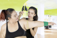 Trainer measuring arm of fat woman Stock Images